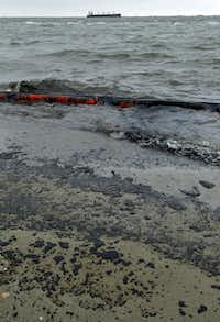 Heavy crude oil washes over booms and onto the beach along Boddeker Road in Galveston.(Jennifer Reynolds - The Daily News)