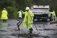 Floyd Taylor, with the City of Austin Watershed Protection department, cleaned debris that had washed onto a roadway Saturday.(Ralph Barrera - AP)