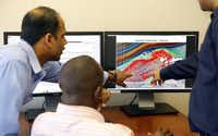 From left: Pioneer Natural Resources engineers John Ndungu, (left) Omkar Jaripatke (center) and Nimish Pandya discuss fracking modules at their office in Irving.(Tom Fox - Staff Photographer)