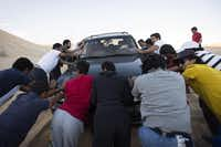 San Diego State students push one of their vehicles after it got stuck in the sand in Glamis, a popular section of the Imperial Dunes in southeastern California, on March 9, 2014.Josh Morgan  -  MCT