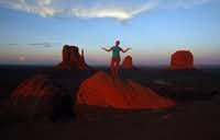 The sun sets over Monument Valley in Arizona while visitors pose for pictures on the red rocks.