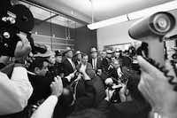 Lee Harvey Oswald is surrounded by media.