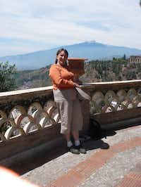 Part-time Addison resident Teresa Wilkin, shown here in front of active volcano Mount Aetna in Sicily, Italy.