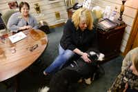 Melody Brockway pets Candy, a grief therapy dog at Rest Haven funeral home in Rockwall, while making her pre-arranged funeral plans with Debbie Dooley, the funeral home's family service professional. Candy is being trained to take part in the funeral arrangement and visitation process, to comfort guests and relieve stressful situations.(ROSE BACA)
