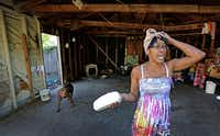 "Lacye Crow talks  about the cracked beam in the garage of her home on Harding Street in Dallas. She's also gone six months without running water because of a previous tenant's unpaid bill. She said pleas to Dennis Topletz are met by: ""That's not my fault. I'm not fixing it.""(Louis DeLuca - Staff Photographer)"
