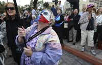 With her face painted like a Texas flag, Lynn Jones of Mesquite hoisted a video camera to record the return of the letter written by William Barret Travis to the Alamo during a ceremony Friday.