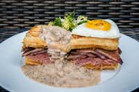 his undated image provided by The Little Nell hotel in Aspen, Colo., shows the Three Little Piggies breakfast sandwich, served at the hotel's Element 47 restaurant. The dish consists of a quarter-pound of slow-roasted shaved porchetta, smoked and pan-seared pork belly and house-made sausage gravy, resting on top of an egg-battered French toast waffle, topped off with a fried farm egg. It's one of a number of over-the-top yummy comfort foods being served at ski resorts this season.