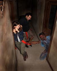 This August 2013 image provided by Shocktoberfest shows an actor portraying a zombie grabs a flag from the belt of someone walking through the Prison of the Dead Escape, part of the Shocktoberfest attraction in Reading, Pa.