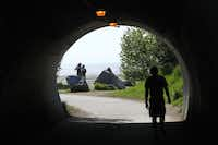 This photo taken June 11, 2013, shows a man running in a tunnel along the Tony Knowles Coastal Trail in downtown, Anchorage, Alaska, while others admire Cook Inlet. Anchorage offers more than 135 miles of multi-use trails in the city.