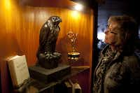 "In this photo taken Thursday, Sept. 27, 2012, Gloria Para of San Francisco, looks at a replica of the Maltese Falcon at John's Grill in San Francisco. San Francisco has a long history as a favorite site for filmmakers and the movie buffs who want to see the spots where their favorite scenes took place, from Fort Point under the Golden Gate Bridge where Jimmy Stewart saved Kim Novak in ""Vertigo"" to the steps of City Hall, where Sean Penn gave an impassioned speech in ""Milk,"" to Alcatraz, stage for Clint Eastwood and many others. One of the city's oldest restaurants, the grill was a setting in author Dashiell Hammett's a¢,ǨaìThe Maltese Falcon.a¢,Ǩ¬ù The interior looks just as you would picture it from the book, filled with original period furnishings. The walls are covered with photos of famous customers and the second floor has a replica of the falcon, along with movie stills and foreign translations of the novel. (AP Photo/Eric Risberg)"