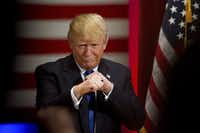 Republican presidential candidate Donald Trump poses with a ring given to him by a group of veterans during a campaign event on the campus of Drake University, Thursday, Jan. 28, 2016, in Des Moines, Iowa. (AP Photo/Andrew Harnik)