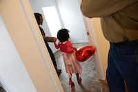 Ethiopia Tuffa leads her daughter Hamera, 4, into her new bedroom during dedication ceremony for the family's new home on April 7 in Plano. The four-bedroom home was built by Habitat for Humanity and will provide more space for their three children, including their 17-month-old Caleb, who has a rare genetic condition called Prader-Willi syndrome that causes low muscle tone, short stature if not treated and a chronic feeling of hunger.( Rose Baca  -  neighborsgo staff photographer )