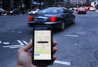 An UBER application is shown as cars drive by in Washington, DC on March 25, 2015. (AFP PHOTO/ ANDREW CABALLERO-REYNOLDS)