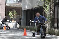 The Beck Group employees race giant, adult-sized tricycles.