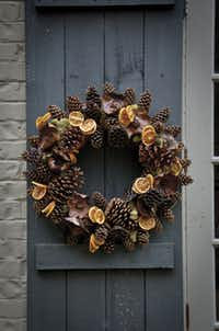 Slightly varnished pinecones in a mix of shapes and sizes placed in reindeer moss accented with lotus pods and wrapped cinnamon sticks add tonal interest to this beautiful wreath. $199 at jamesfarmer.com