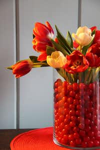 Use two glass cylindrical vases, one narrower than the other but about the same height or a bit shorter, for a fool-the-eye effect. Put cut flowers in a narrower vase that is placed inside the bigger vase and fill in the gap with candies, crushed colored glass or any other interesting filler.
