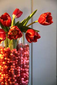 Jelly beans fill in the dry gap between a smaller cylindrical vase fit inside a larger vase the same shape. Water and flowers go inside the smaller vase surrounded by candies.