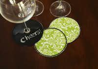 Coasters can be slipped on stemware to help guests keep track of their drinks. The cotton reverse can be used as a regular coaster. $12.50 for pack of four.