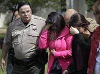 A member of the Glenn County Sheriff's Department escorts distraught people from Memorial Hall, where the Red Cross set up after Thursday's accident. Among the dead were the drivers of the bus and the FedEx truck, five Los Angeles area students and three adult chaperones.(Rick Loomis - MCT)