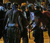 Protesters try unsuccessfully to light a Molotov cocktail as the police prepare to advance on Wednesday, Aug. 13, 2014, in Ferguson, Mo. It was the fourth night of unrest in Ferguson after the fatal police shooting of a teen on Saturday. (Chris Lee/St. Louis Post-Dispatch/MCT)Chris Lee - MCT