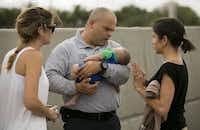 Miami-Dade Fire paramedic lieutenant Alvaro Tonanez helps rescue 5-month-old Sebastian de la Cruz, who stopped breathing. At right, the baby's aunt, Pamela Rauseo, performed CPR after pulling over her SUV on the side of the road along Florida state road 836, just east of 57th Avenue, around on Thursday, Feb. 20, 2014. At left is Lucila Godoy, who stopped her car to assist with CPR. (Al Diaz/Miami Herald/MCT)Al Diaz - MCT