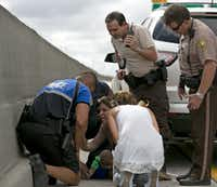 Rescuers assist Pamela Rauseo, center, who performed CPR on her nephew, 5-month-old Sebastian de la Cruz, after pulling over her SUV on the side of the road along Florida state road 836, just east of 57th Avenue, around on Thursday, Feb. 20, 2014. At right is Lucila Godoy, who stopped her car to assist in the rescue. At left is Sweetwater, Fla., officer Amauris Bastidas who also stopped to the aide the baby. (Al Diaz/Miami Herald/MCT)Al Diaz - MCT