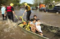 Isabel Rodriguez and her children Christopher, left, 3, and Rubi, 8 months, are carried on a boat on Quicksilver Boulevard in Austin, Texas, after their home on South Pleasant Valley Road was flooded on Thursday October 31, 2013. (Jay Janner/Austin American-Statesman/MCT)(Jay Janner - MCT)