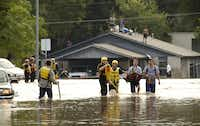 Tyler Pinnell, second from right, and his roommate Taylor McIntyre, wlak through the floodwaters on Quicksilver Boulevard in Austin, Texas, after leaving their flooded home on Canella Drive on Thursday, October 31, 2013. (Jay Janner/Austin American-Statesman/MCT)(Jay Janner - MCT)