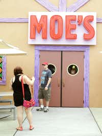 "In this Sept. 5, 2013 photo, guests snap photos at the entrance to Moe's Tavern in ""The Simpson's"" themed Springfield USA at Universal Orlando in Orlando, Fla."