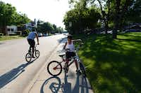 Keilob Blaylock, 10, rides his bike with his uncle along Timberglen Road in Dallas. The area ranks No. 1 for urban sophisticates in Plano, Murphy and Wylie.