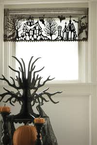 DRESSED TO THRILL: The Spooky Hollow Valance transforms more than windows -- it can also shroud a mantel, table or lamp in haunted house web-like lace. $19.95. www.plowhearth.com.