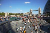 Families sitting in the sunshine on the Southbank, Tower Bridge in background( Pawel Libera  -  London and Partners )