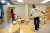 Kenneth Sherman, early childhood educator, and Shanna Malone, early childhood curriculum coordinator, move furniture into a classroom at Vogel Alcove's new facility, the City Park Elementary building in Dallas. The nonprofit acts as a daycare center for children who live in homeless shelters, domestic violence shelters and transitional housing in the Dallas area.Rose Baca - neighborsgo staff photographer
