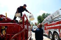 Craig Merritt (left), a part-time volunteer firefighter for the city of Rockwall, hands a container of soap to driver Justin Barker at the Benny Grace Memorial Fire Station in Rockwall.( Photo by ROSE BACA  - neighborsgo staff photographer)