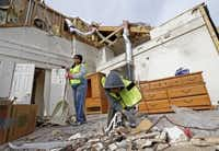 Volunteers Beatriz Rivera, left, and her 5-year-old son Kellan Rivera, clean up debris at a house that has been damaged by the tornadoes last week in Garland, Texas, Friday, Jan. 1, 2016. (Jae S. Lee/The Dallas Morning News)