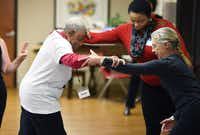 Sadie Armstrong gets help from Sarah Nwosu and Judy Cooper (right) in a balance class at Holy Cross Hospital's Senior Source center in Silver Spring, Md.( Matt McClain  -  The Washington Post )