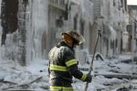 A Philadelphia firefighter works the scene of an overnight blaze in west Philadelphia, Monday Feb. 16, 2015, as ice formed from where the water from the fire hoses froze.(Jacqueline Larma - AP)
