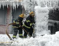 Philadelphia firefighters work to free equipment at the scene of an overnight blaze in west Philadelphia, Monday Feb. 16, 2015, as ice formed from the water used to fight the fire.(Jacqueline Larma - AP)