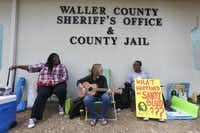 Carie Cauley, left, Rev. Hannah Bonner and Rhys Caraway protest, after the death of Sandra Bland, as they sit in front of the Waller County Sheriff's Office and county jail on Monday, July 20, 2015, in Hempstead, Texas. Authorities said Bland hanged herself in the jail three days after being pulled over by police for a traffic violation and then arrested for allegedly kicking an officer during the stop. Bland's family is ordering an independent autopsy, lawyers said. (Karen Warren/Houston Chronicle via AP) MANDATORY CREDIT(Karen Warren - AP)