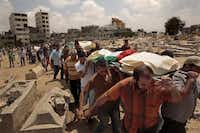 Palestinian friends and family gathered Monday to bury their dead at a cemetery in the Gaza Strip. Seven members of the Hallaq family were killed by Israeli forces.( Carolyn Cole  -  Los Angeles Times )