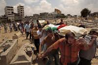 Palestinian friends and family gathered Monday to bury their dead at a cemetery in the Gaza Strip. Seven members of the Hallaq family were killed by Israeli forces.Carolyn Cole  -  Los Angeles Times