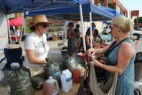 Heather Rinaldi, co-owner of Texas Worm Ranch, helps customer Nita Melcher shop for fertilizer products at the White Rock Local Market.