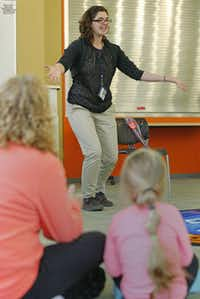 Jenna Yoder (center) tells stories to Nova Nelson, 3, (right) and her nanny, Cindy Shockley, during Boogie Woogie Books at White Rock Hills branch library.(Staff photo by Nathan Hunsinger - DMN)