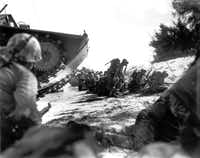 The first wave  of U.S. Marines to hit the shore at Saipan in June 1944 sought cover behind a sand dune while they awaited the following three assault waves.(The Associated Press)