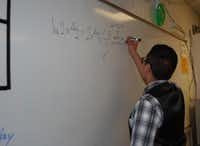 Lopez occasionally uses the whiteboard in Grant Ashmore's class to work equations. Ashmore said Lopez is completing the work on his own, but sometimes bounces ideas off of him.(Staff photos by ANANDA BOARDMAN)