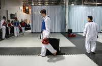 <TypographyTag12>Coppell High School student Connor Wilson</TypographyTag12>, 16, walks across the mat after a sparring session led by his instructor, Sang Cha. <252>Staff photos by <TypographyTag11>Rose Baca</TypographyTag11>