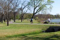 People run and cycle along the White Rock Lake Trail at Winfrey Point. The White Rock Lake Conservancy will hold Celebration! White Rock there on Thursday.Ananda Boardman - neighborsgo staff
