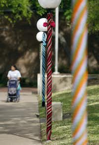 Yarn bombers like to use bright colors and sturdy yarn for their work. These three striped poles are near the Lakewood Branch Library in Dallas.