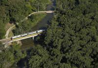 A DART Blue Line train passes over White Rock Creek Trail. When the rail system was pitched to voters in 1983, its supporters touted reductions in traffic congestion and using DART to encourage development.