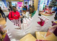 Margie Harris, left, Jonshericka Jimerson, 17, center, and Jada Jimerson, 16, shop for scented lotions at Bath & Body Works at Town East Mall on Wednesday, December 17, 2014. (Ashley Landis/The Dallas Morning News)(Ashley Landis - Staff Photographer)